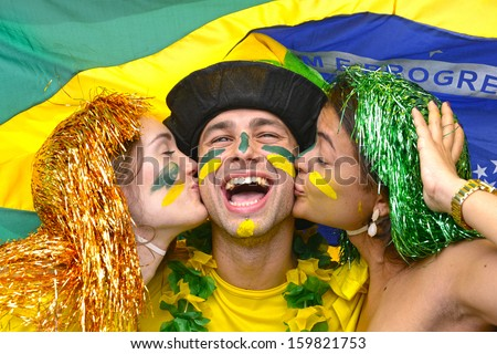 Group of multiethnic young adult fans celebrating victory of the Brazilian soccer team kissing each other