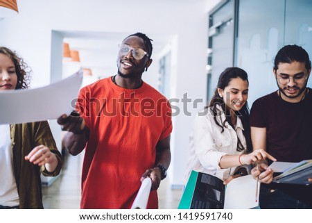Group of multiethnic young men and women chatting and discussing paper drafts while walking together in hallway of modern office