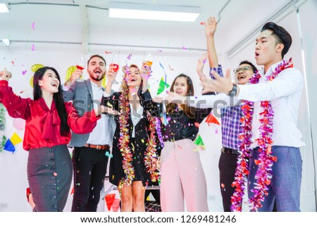 Group of multiethnic young people having an office party indoor.