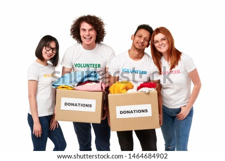 Group of multiethnic young people in volunteer T-shirts holding carton boxes with donations and smiling for camera while standing against white background