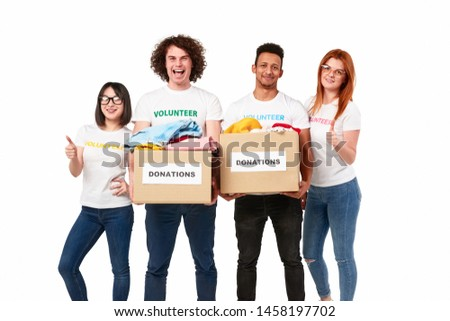 Group of multiethnic young people with donation boxes smiling and showing thumb up gesture while participating in charity movement against white background