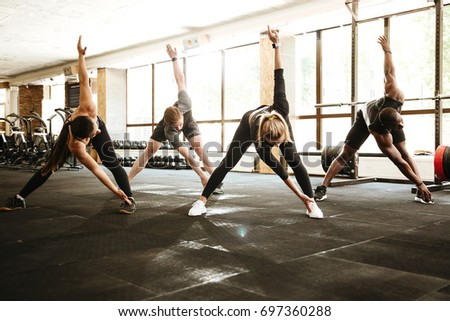 Group of multiethnic young people working out together at the gym
