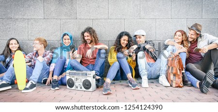 Group of multiracial friends having fun outdoor - Millennial young people using mobile phones taking photo and listening music with vintage stereo - Generation z, social and youth lifestyle concept
