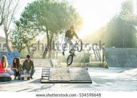 Group of multiracial friends watching a biker performing freestyle jump with bmx bicycle - Young people having fun with extreme sport recreation in urban city park - Focus on right man - Warm filter