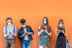 group of multiracial friends with face masks in front of orange wall using smartphones to sharing content on social networks