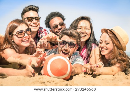 Group of multiracial happy friends having fun at beach games - International concept of summer joy and multi cultural friendship together - Warm sunny afternoon color tones with shallow depth of field