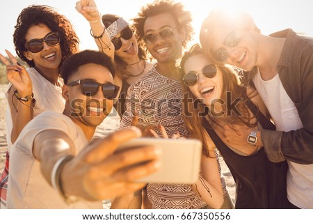 Group of multiracial happy friends taking selfie and having fun on a beach