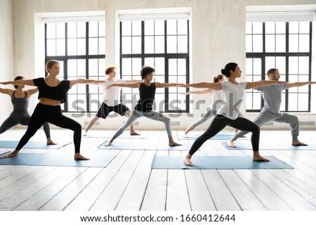 Photo of  Group of multiracial people practicing yoga asanas, doing Warrior Two Virabhadrasana 2, work out indoors full length, posture increases stamina and flexibility, improves physical and mental endurance