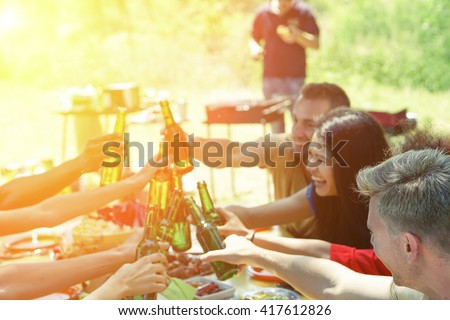 Group of multiracial students having barbecue on a sunny day - Young cheerful people cheering with beer bottles on summer time - Concept about good and positive mood with friends - Focus on blonde guy #417612826