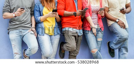 Group of multiracial students watching smart mobile phones in university break - Young people addiction to new technology trends - Alienation moment for new generation problem - Focus on center hands