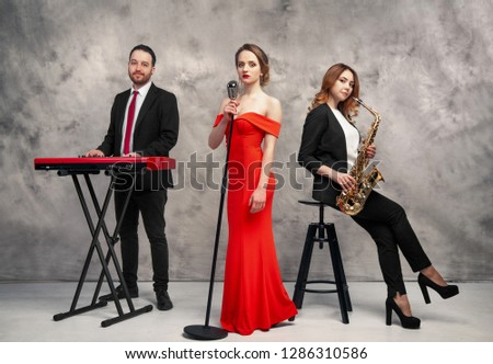group of musicians, a girl with a saxophone, a singer with a microphone and a guy playing the keys, in full growth #1286310586