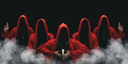 Group of mysterious figures in hooded cloaks in the dark. Leader of sectarians holds skull with horns. Horror scene with smoke. Black background.