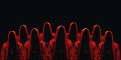 Group of mystery people in a red hooded cloaks. Isolated on black. Unrecognizable person. Hiding face in shadow. Ghostly figure. Sectarians. Conspiracy concept.