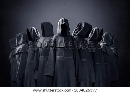 Group of nine scary figures in hooded cloaks in the dark Foto stock ©