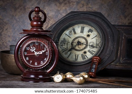Group of objects on wood table. old clock, hourglass, antique wooden clock ,Still life