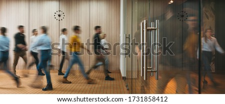 Photo of  Group of office people walking at office open space. Team of business employees at coworking center. People at motion blur. Concept working at action