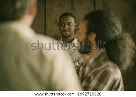 Group Of Office Workers Communicates During A Break While Standing In Office, Focus On Charming Smiling African Guy Thoughtfully Listening To His Colegs, Standing In Blurred Foreground Imagine de stoc ©