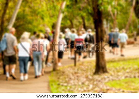group of old and healthy people walking in the nature, blurred