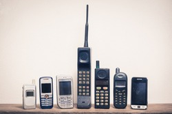 Group of old and obsolete mobile phone or cell phone on old wood with a light rough background