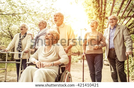 Group of old people walking outdoor. Crew with old friends, walking in the park