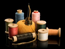 Group of old wooden and cardboard coils with multi-colored threads, hank of threads for darning, needle and brass thimble it is isolated on black