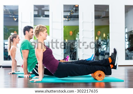 Group of one man and two women doing roll gymnastics on floor of gym or fitness club