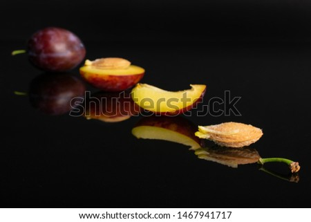 Group of one whole one half one quarter two pieces of fresh blue plum with a stone placed diagonally in line isolated on black glass #1467941717
