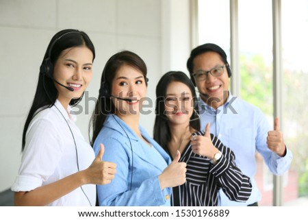 group of operators with headset show thumb up in office
