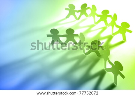 Group of paper-chain people holding hands. Blue and green colors. Copy space - stock photo