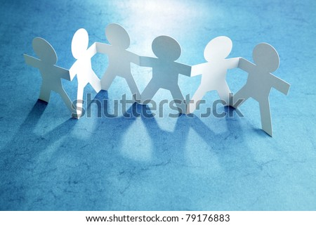 Group of paper chain people holding hands together. Teamwork concept
