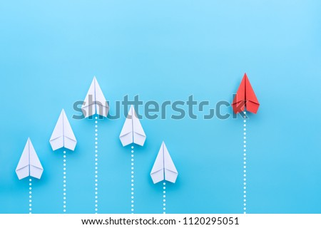 Group of paper plane in one direction and with one individual pointing in the different way on blue background. Business for innovative solution concept.