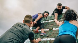 Group of participants in an obstacle course climbing a net
