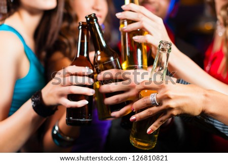 Group of party people men and women drinking beer in a pub or bar