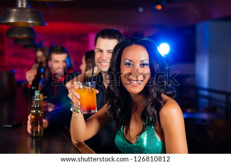 Group of party people with cocktails in a bar or club having fun, one woman is looking into the camera
