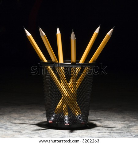 Group of pencils in a wire mesh pencil holder. - stock photo