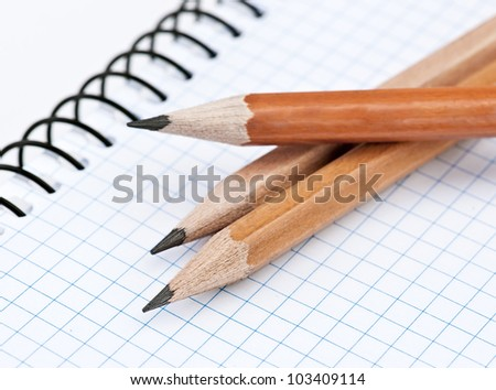 group of pencils on squared spiral notebook - stock photo