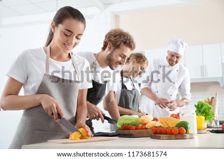 Group of people and male chef at cooking classes