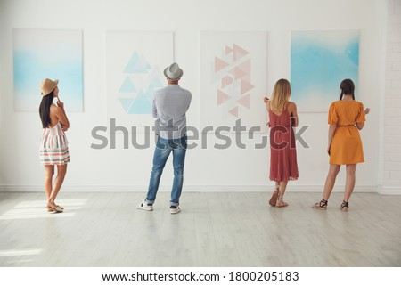 Group of people at exhibition in art gallery, back view