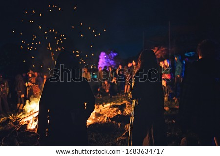 Group of people at party camp fire with campfire song and campfire meals playing campfire games and eating camp fire grill, telling campfire stories near the fire with wood, flames in the nature night