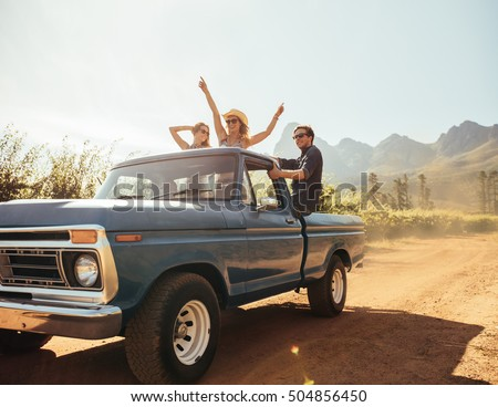 Group of people at the back of a pick up truck having fun. Young men and women enjoying on a road trip in countryside on a sunny day.