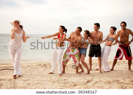Group of people at the beach pulling a rope
