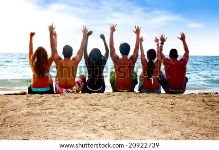 group of people at the beach with arms up