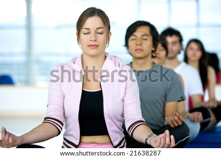 group of people at the gym doing yoga and meditation exercises
