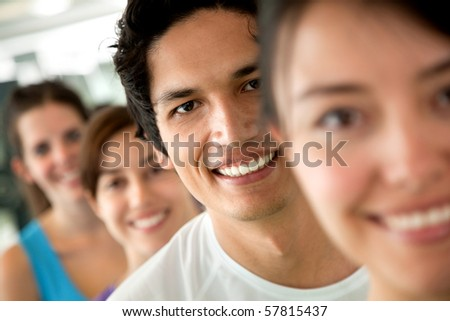 group of people at the gym in a row and smiling