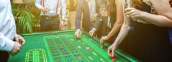 Group of people behind roulette gambling table in luxury casino. Friends playing poker at roulette table with tape measure. Vegas games nightlife lucky winning concept. Banner