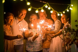 group of people celebrate an event like new years eve or birthday all together with sparkles light by night in the dark. smiles and having fun in friendship for different ages men and women at home.