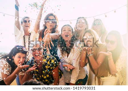 Group of people celebrate together having a lot of fun blowing coloured confetti - friendship and diversity ages generation laugh and smile on party - cheerful joyful concept for ladies