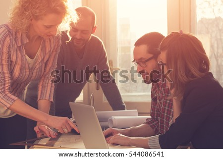 Group of people discussing business plans, with lap-tops, plans in a room lit by natural sunlight.