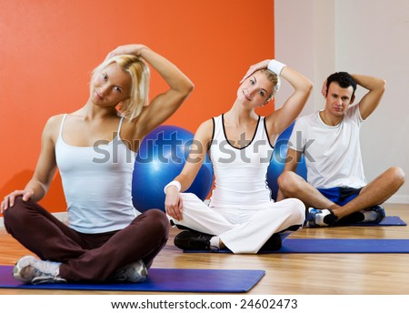 Group of people doing yoga exercise (focus on woman in the middle)