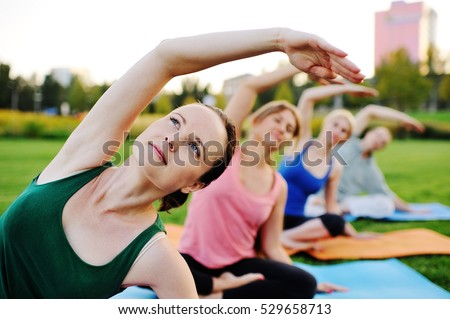 group of people doing yoga on the green with fresh grass outdoors. Healthy lifestyle
